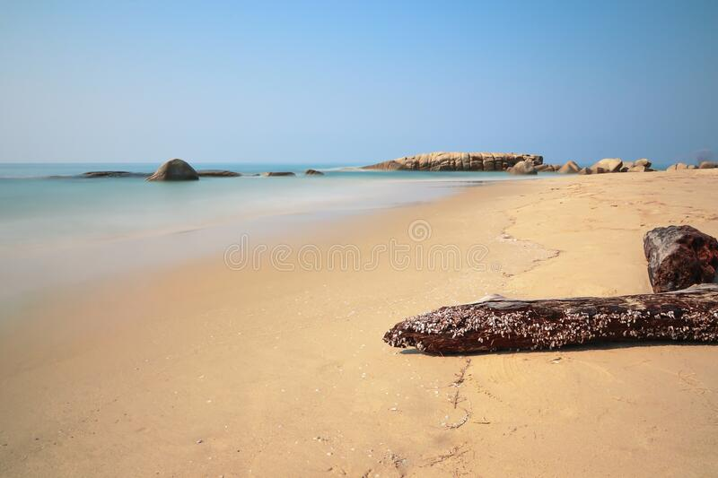 Timber and rock on the beach royalty free stock images