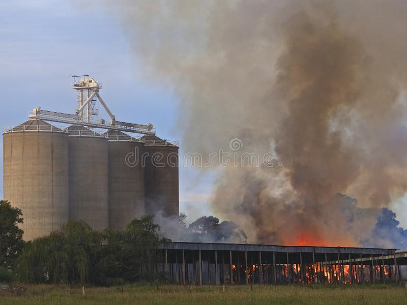 Timber shed on fire burnng under Grain silos stock photos