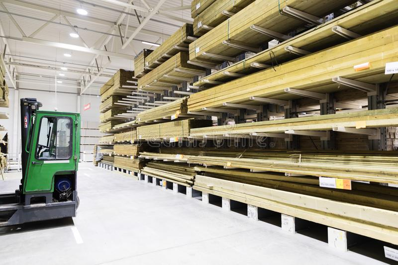 Timber warehouse - shelves with wooden planks and forklift stock image