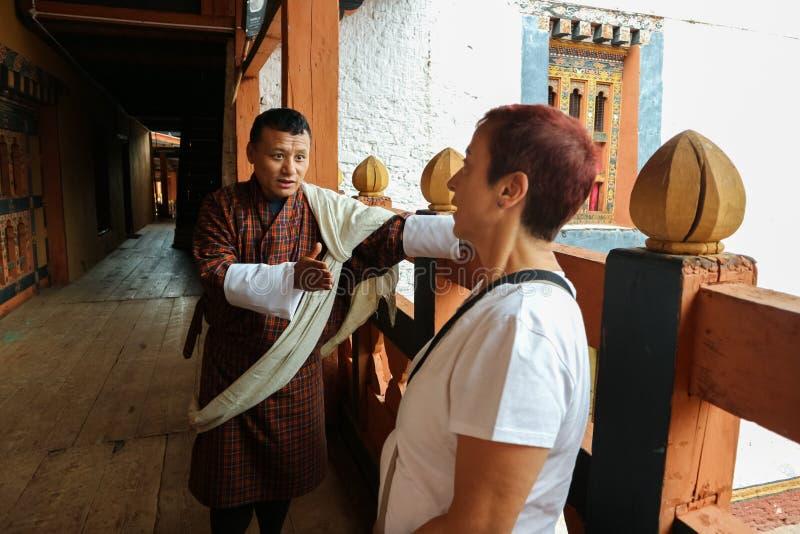 Timbu, Bhután - 10 de septiembre de 2016: Guía turística butanesa que demuestra el templo al turista en el balcón imágenes de archivo libres de regalías