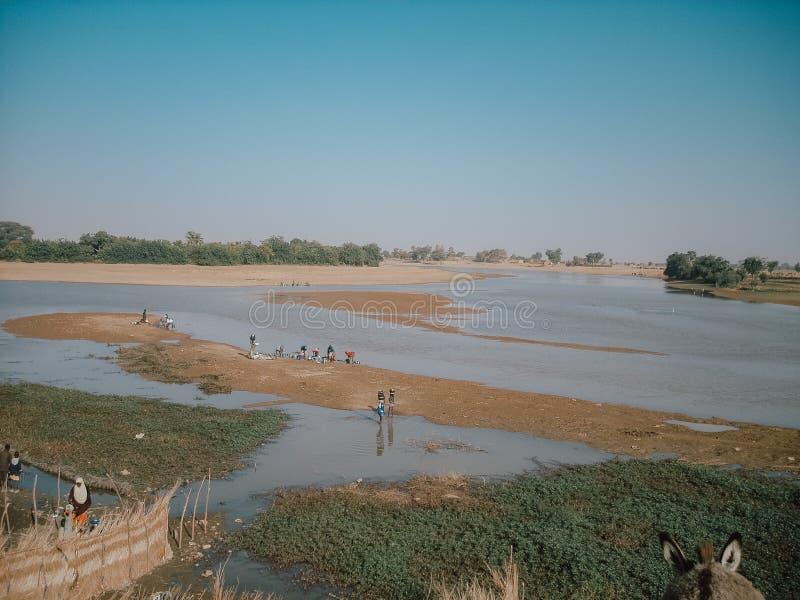 Timbuktu, Mali, África - 3 de fevereiro de 2008: Opinião Niger River com os trabalhadores em sua costa foto de stock royalty free