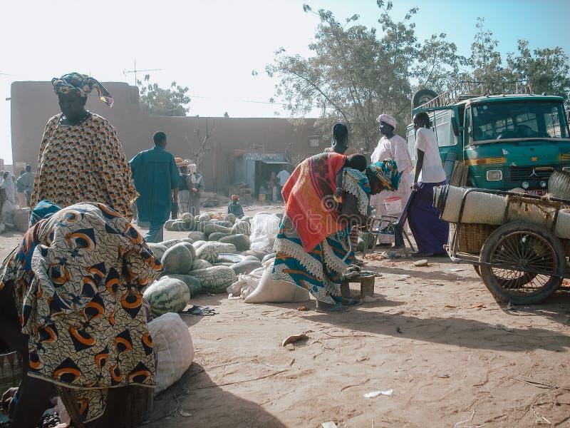 Timbuktu, Mali, África - 3 de fevereiro de 2008: Venda e compra de pessoas no mercado urbano imagem de stock