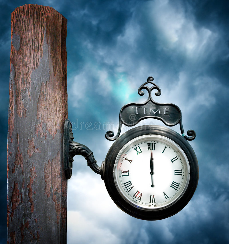 Time. A iron black clock on a worn wooden post with a cloudy stormy backdrop. Concept for eternal time or now is the time or new year royalty free stock photo