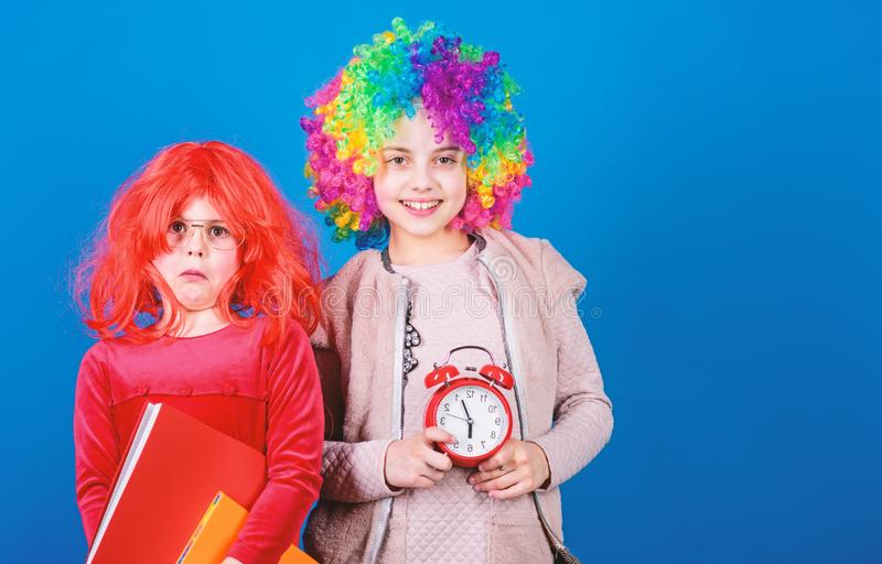 Are we in time. Adorable party goers. Cute children with fancy hair waiting for party time with clock. Little girls royalty free stock images