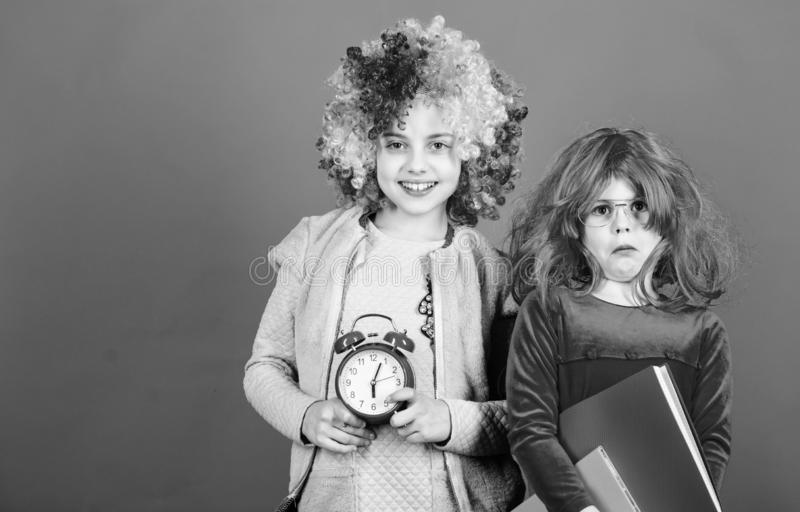 Are we in time. Adorable party goers. Cute children with fancy hair waiting for party time with clock. Little girls stock photos