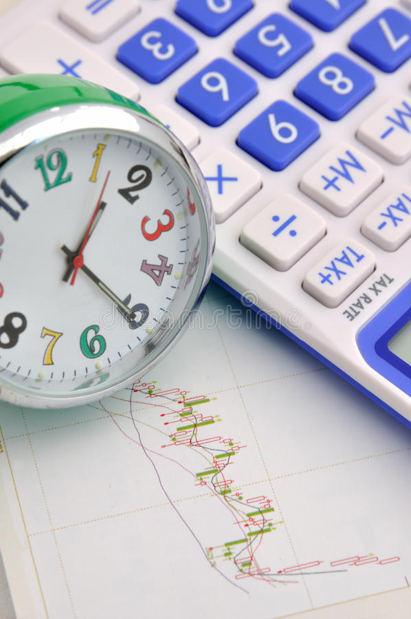 Time and analysis of stock business. A clock and calculator on stock graph sheet, means time and stock value increasing, or stock marketing anaysis, important royalty free stock photos