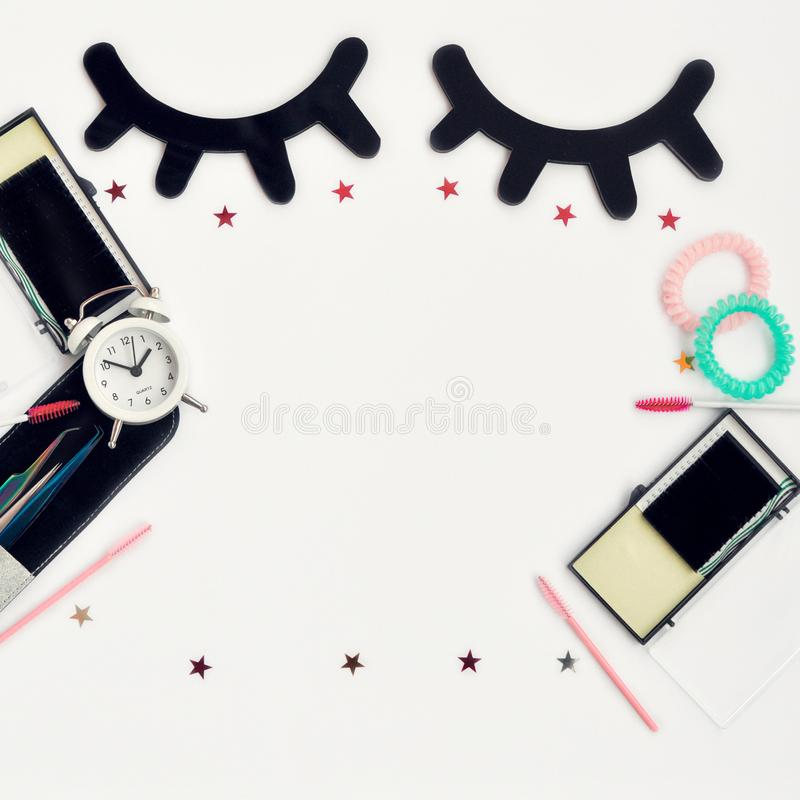 Time for beauty eyelashes and eyebrows: eyelash extension tools and decor on white background with copy space. top view. Flatley. Time for beauty eyelashes and royalty free stock images