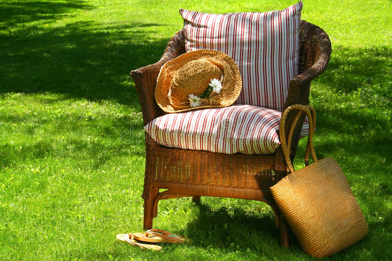 Time for a break. Wicker chair and old summer hat on a hot summer's day stock images