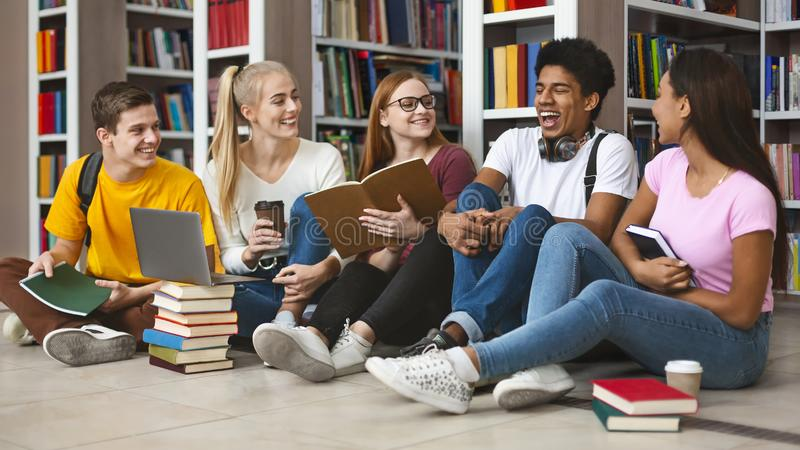 Group of teenage friends laughing while preparing for exams. Time for break. Group of international teenage friends laughing while preparing for school exams royalty free stock photos