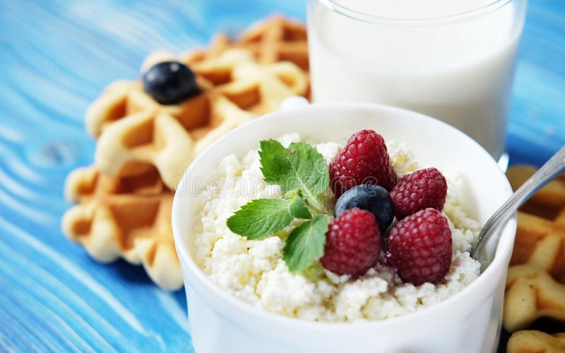 Time for breakfast. Cottage cheese with berries, waffles and milk on a wooden blue background. royalty free stock images