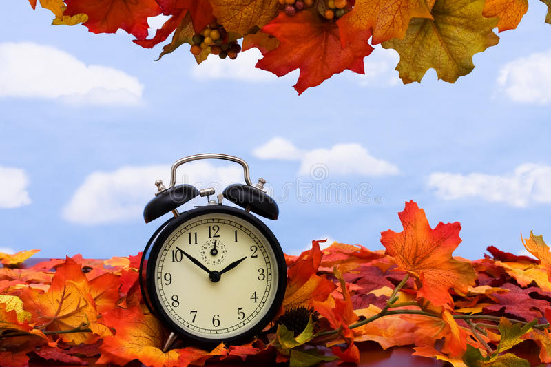 Time change. Fall coloured leaves with a black clock on a sky background, Fall Leaves royalty free stock photos
