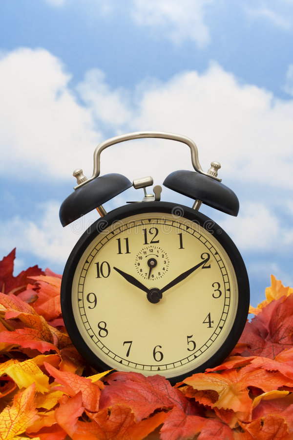 Time Change. Retro clock on fall leaves sky background royalty free stock photo