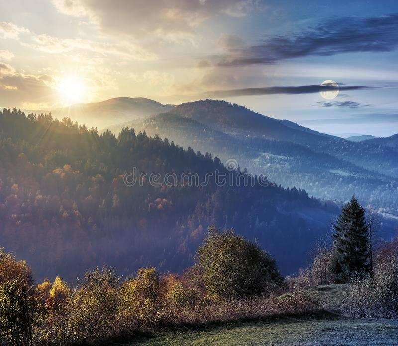 Time change above countryside in mountains. Day and night time change concept above countryside in mountains. trees on the edge of a grassy meadow beneath sun stock image
