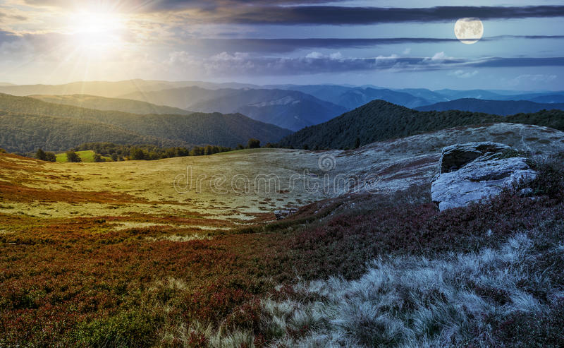 Time change over stones on the edge of mountain hillside. Day and night time change concept image. huge stones among the grass on top of the hillside meadow near stock images
