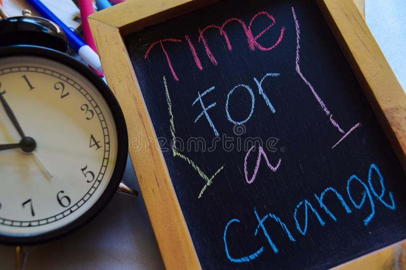 Time for change a on phrase colorful handwritten on chalkboard, alarm clock with motivation and education concepts stock photography