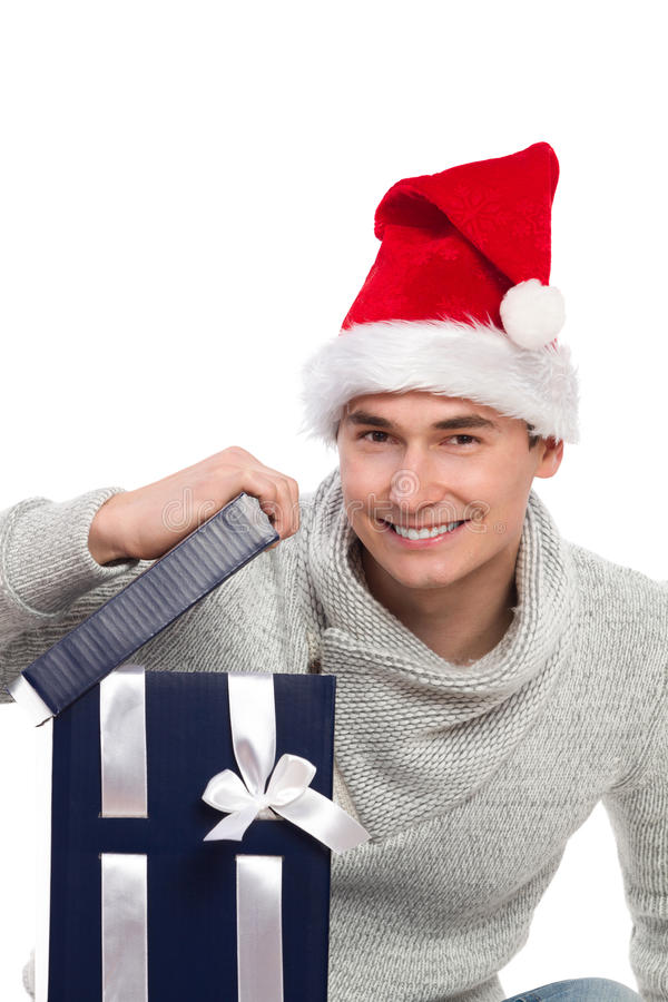 Time for christmas gift. Smiling man in santa's hat opening a gift's lid and looking at camera. Studio portrait isolated on white stock photos