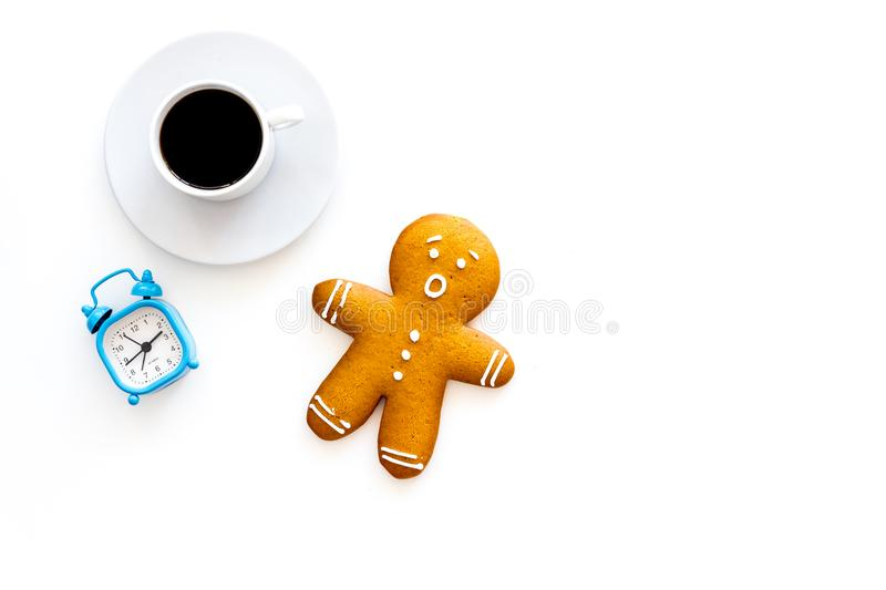 Time for coffee break. Coffee cup near gingerbread man, alarm clock on white background top view copy space. Time for coffee break. Coffee cup near gingerbread stock images