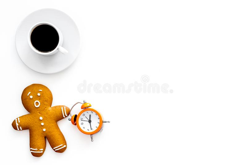 Time for coffee break. Coffee cup near gingerbread man, alarm clock on white background top view copy space. Time for coffee break. Coffee cup near gingerbread royalty free stock image