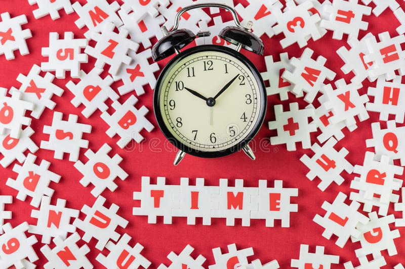 Time concept by abundance of white puzzle jigsaw around and combine word at center as TIME with black retro alarm clock royalty free stock images