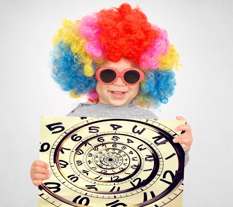 Time concept. Happy child with clown wig holding the clock in drost effect royalty free stock photo