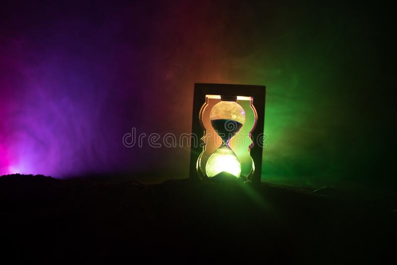 Time concept. Silhouette of Hourglass clock and smoke on dark background with hot yellow orange red blue cold back lighting, or sy stock illustration