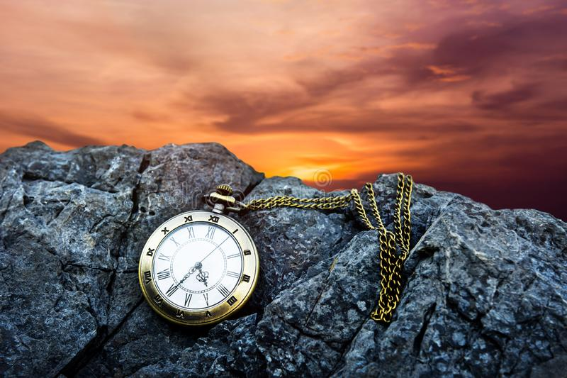 Time Concept. Vintage Golden Pocket Watch on island rock, Sunrise or Sunset Sky as background stock photography