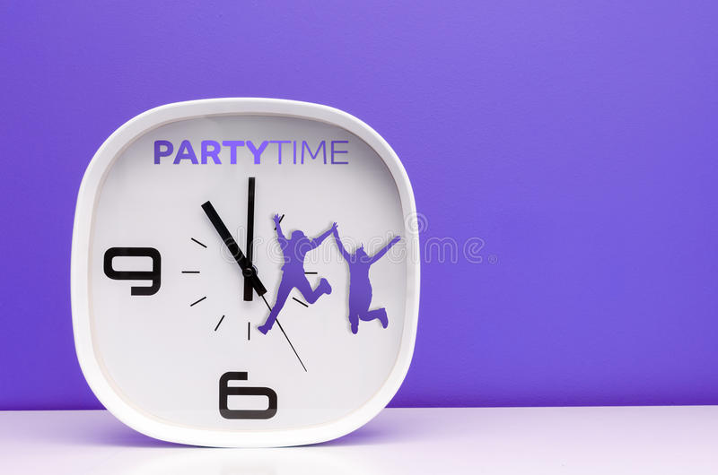 TIme concept white clock. Modern Clock showing party time on colored background and white table royalty free stock image