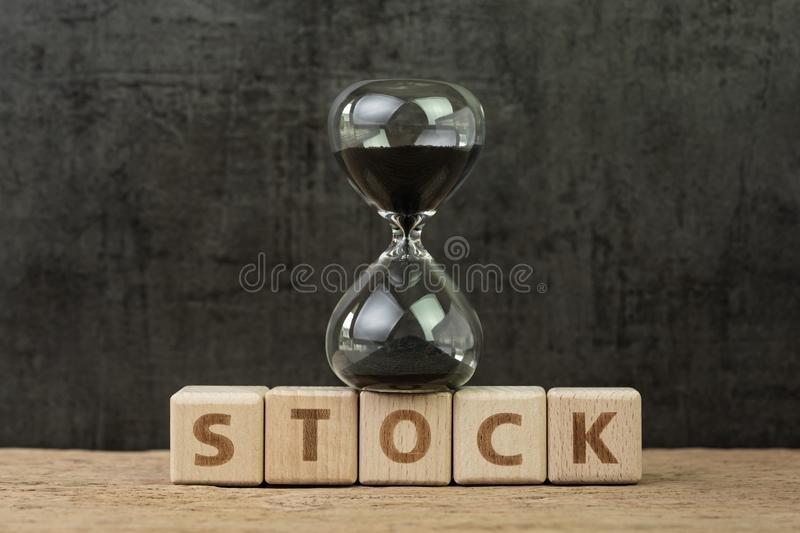 Time countdown for stock market, financial crisis or long term investment, hourglass or sandglass on wooden cube block with royalty free stock photo