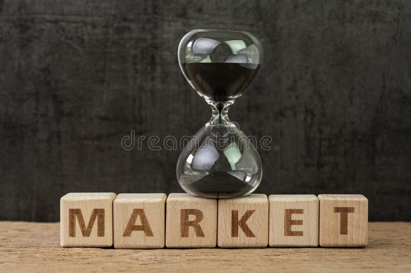 Time countdown for stock market, fluctuation on market, hourglass or sandglass on wooden cube block with alphabet building the stock photo