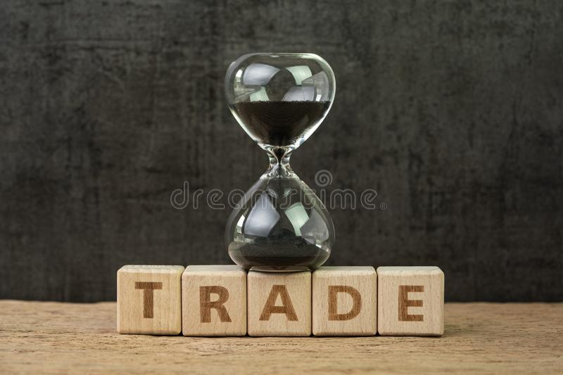 Time countdown for trade war, fluctuation on stock market, hourglass or sandglass on wooden cube block with alphabet building the royalty free stock image