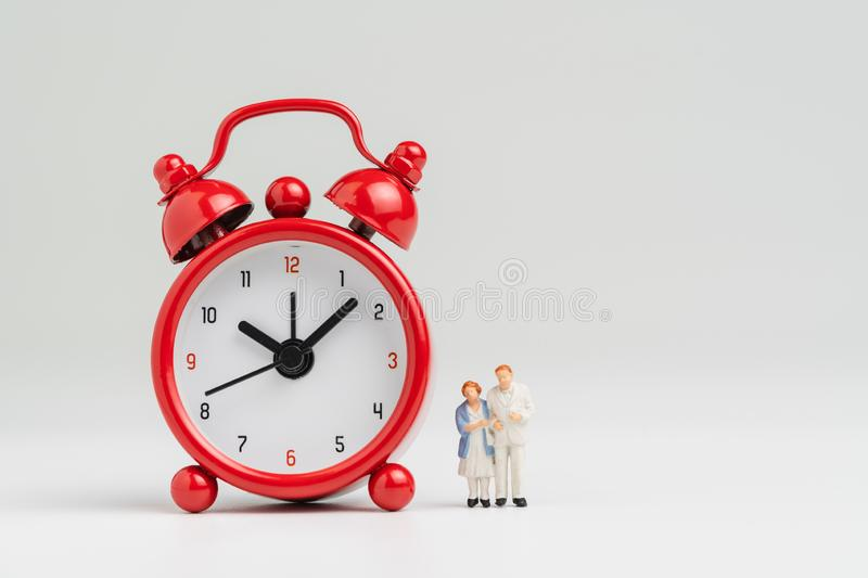 Time counting down for retirement concept, miniature happy senior old couple standing with big red alarm clock on white background royalty free stock images