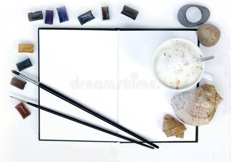 Time for creative and appetizing imaginations. Inspiration object frothy coffee, notebook, paint, sea stones and seashells, flat lay, top view stock image