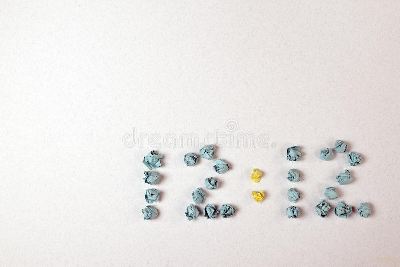 Time. Crumpled pieces of paper in the form of figures are formed 12:12 on a table by the top view royalty free stock images