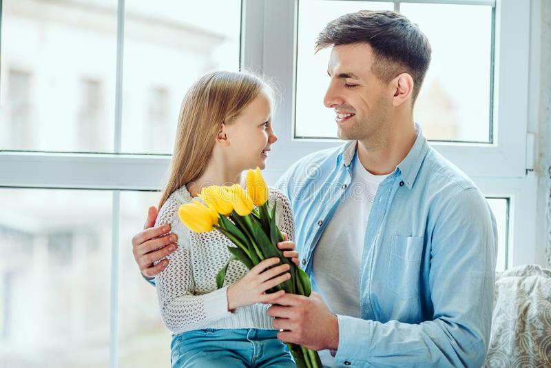 Time with dad is always great.Father gives her daughter a bouquet of tulips stock photo