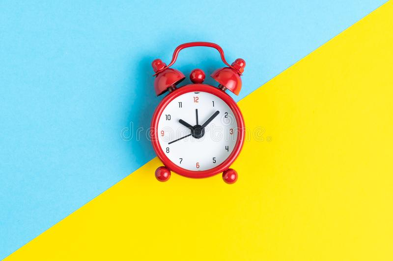 Time, deadline or timer and reminder concept, flat lay of red retro alarm clock on contrast color yellow and blue. background royalty free stock photography
