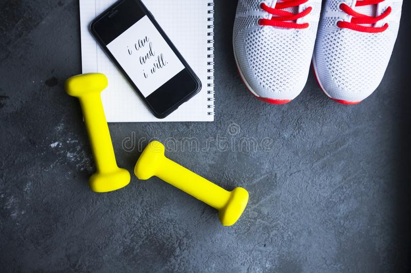 Time for diet slimming weight loss concept. Sport fitness, apple, sneakers, bottle of water and yellow weights on dark stone backg. Round. Vintage retro royalty free stock images