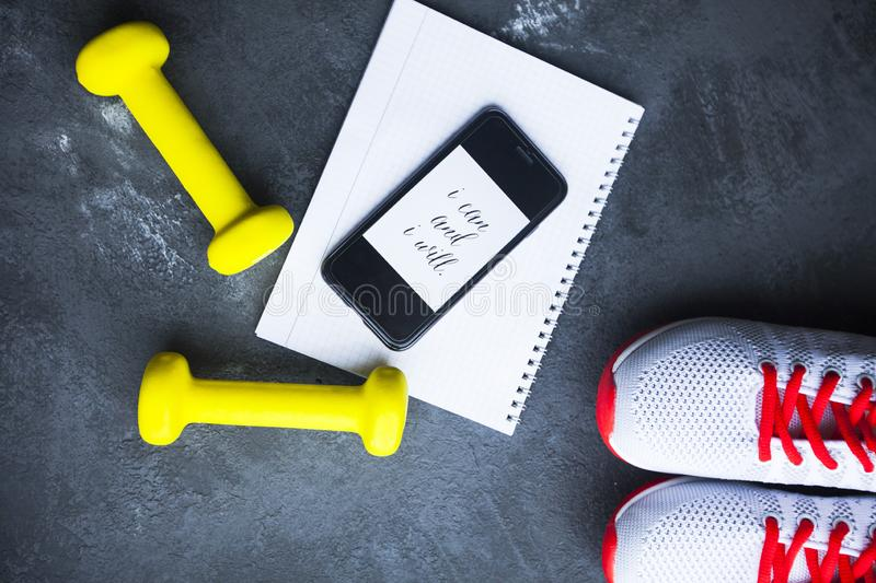 Time for diet slimming weight loss concept. Sport fitness, apple, sneakers, bottle of water and yellow weights on dark stone backg. Round. Vintage retro royalty free stock photos