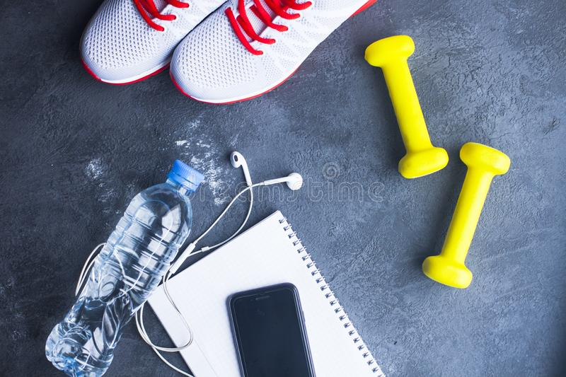 Time for diet slimming weight loss concept. Sport fitness, apple, sneakers, bottle of water and yellow weights on dark stone backg. Round. Vintage retro royalty free stock photography