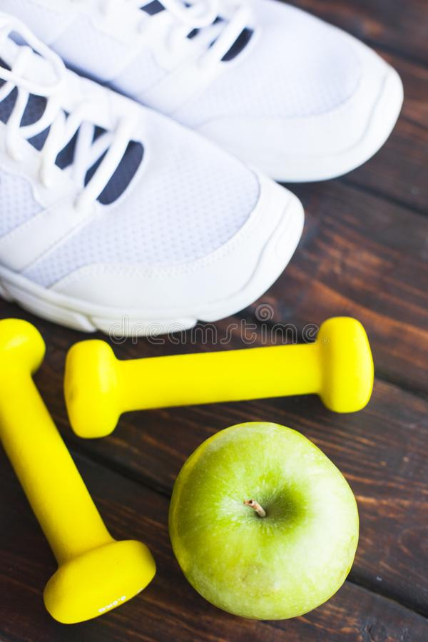 Time for diet slimming weight loss concept. Sport fitness, apple, sneakers, bottle of water and yellow weights on dark wooden back. Ground. Vintage retro royalty free stock photography