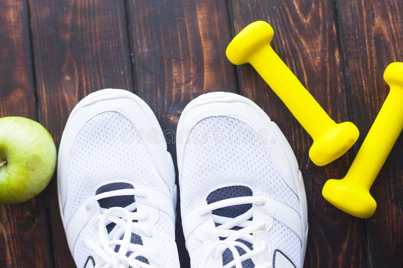Time for diet slimming weight loss concept. Sport fitness, apple, sneakers, bottle of water and yellow weights on dark wooden back. Ground. Vintage retro stock image