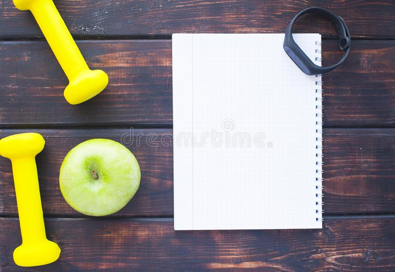 Time for diet slimming weight loss concept. Sport fitness, apple, sneakers, bottle of water and yellow weights on dark wooden back. Ground. Vintage retro royalty free stock photo