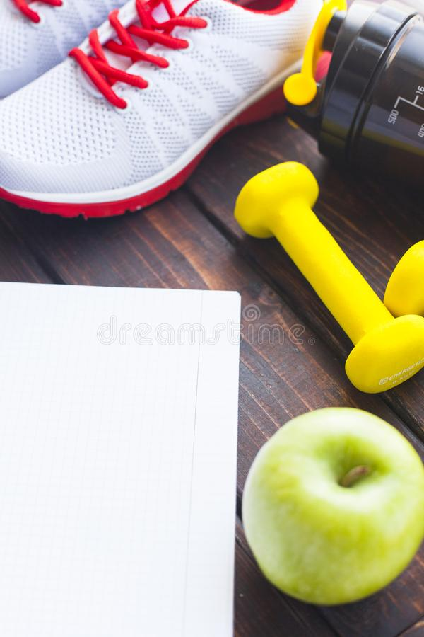 Time for diet slimming weight loss concept. Sport fitness, apple, sneakers, bottle of water and yellow weights on dark wooden back. Ground. Vintage retro stock images