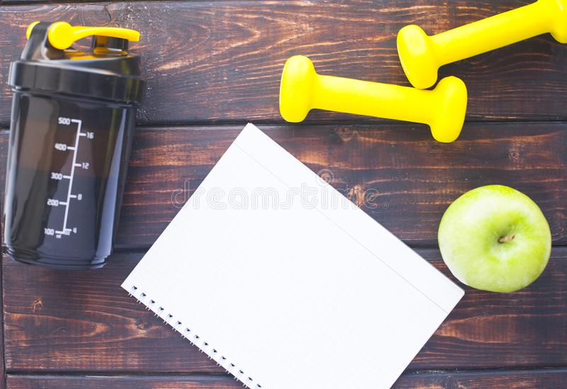 Time for diet slimming weight loss concept. Sport fitness, apple, sneakers, bottle of water and yellow weights on dark wooden back. Ground. Vintage retro stock photo
