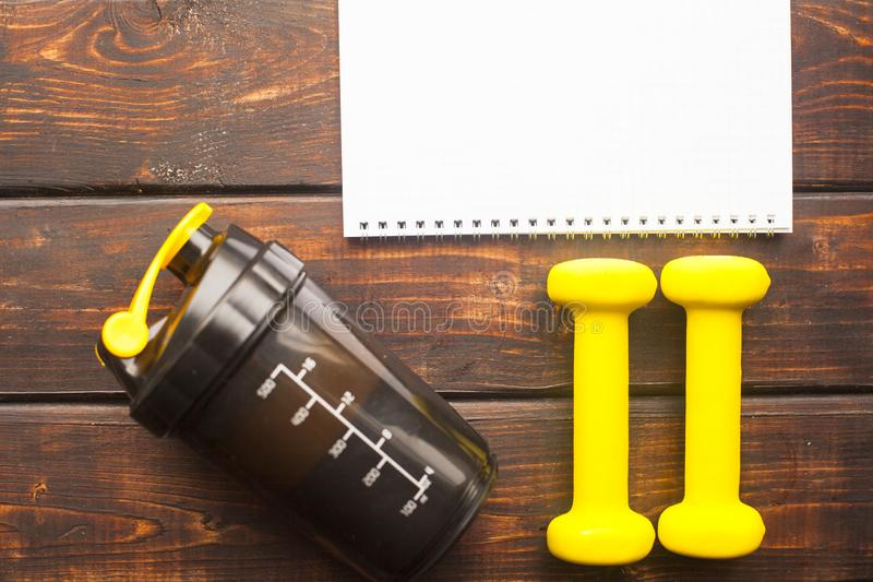 Time for diet slimming weight loss concept. Sport fitness, apple, sneakers, bottle of water and yellow weights on dark wooden back. Ground. Vintage retro stock photography