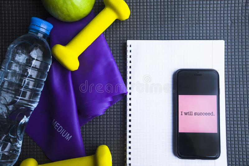 Time for diet slimming weight loss concept. Sport fitness, apple, sneakers, bottle of water and yellow weights on grey rubber back. Ground. Vintage retro royalty free stock photography
