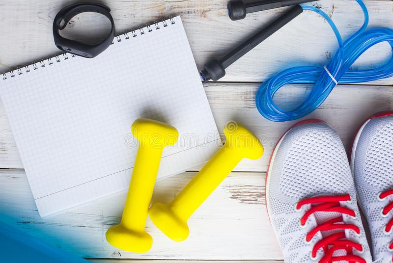 Time for diet slimming weight loss concept. Sport fitness, apple, sneakers, bottle of water and yellow weights on white wooden bac. Kground. Vintage retro royalty free stock image