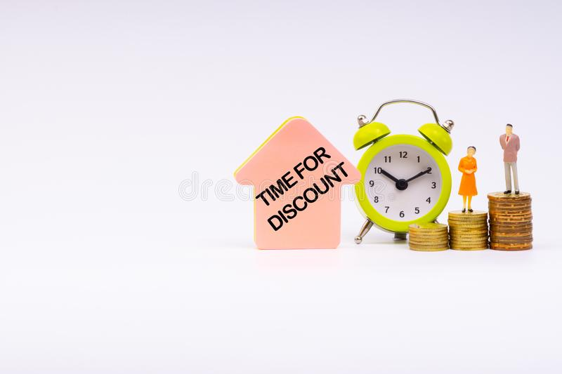 TIME FOR DISCOUNT inscription written, alarm clock, coins and businessman miniature royalty free stock image