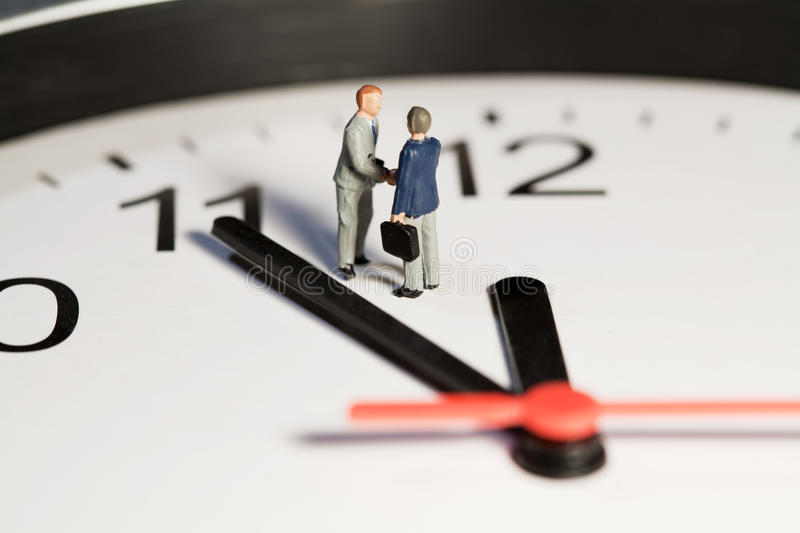 Time Is Of The Essence. Two miniature businessmen toy models shake hands to seal a business deal while standing on the face of a clock alongside the hands royalty free stock photos