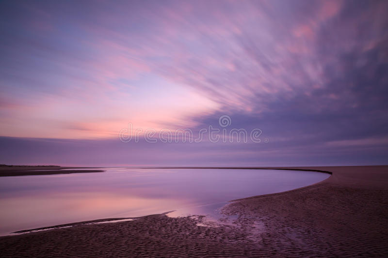 Time exposure of Siltcoos River and moving clouds. At sunset creates a beautiful graphic image royalty free stock photo