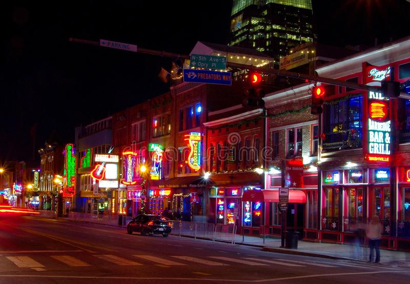 Time exposure of traffic passing by neon signs of bars in Nashville entertainment district at night royalty free stock photos